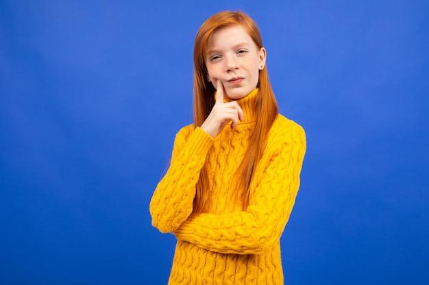 Jolie fille rousse caucasienne dans un pull jaune raisonnement sur bleu