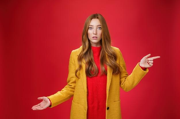 Jolie fille rousse confuse et interrogée en manteau d'automne jaune pointant vers la droite en haussant les épaules en faisant un geste désemparé avec la bouche ouverte à la main se demandait comme posant une question sur fond rouge.