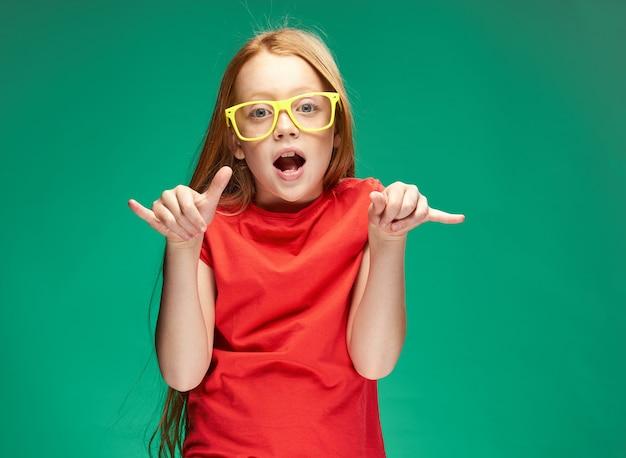 Jolie fille rousse faisant des gestes avec ses mains école verte enfance