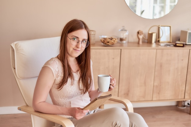 Jolie fille rousse à lunettes qui est assise dans un fauteuil et tient un carnet de croquis dans un intérieur confortable