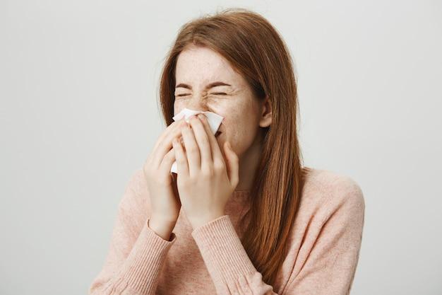 Jolie fille rousse malade avec une allergie éternue dans une serviette