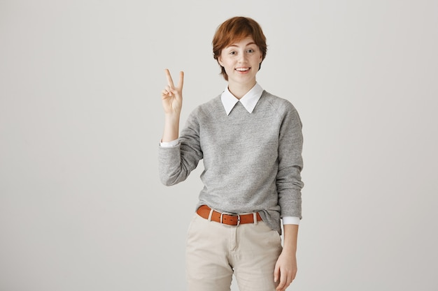 Jolie fille rousse souriante avec coupe de cheveux courte posant contre le mur blanc
