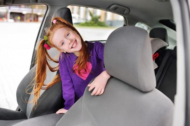 Jolie fille rousse souriante dans le salon de l'automobile