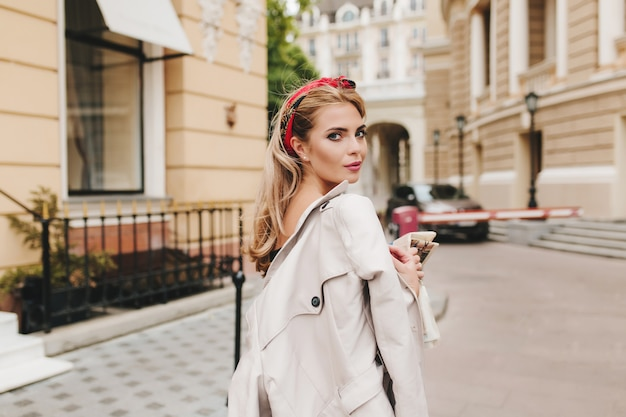 Jolie fille avec ruban rouge dans les cheveux blonds regardant par-dessus l'épaule, explorant les rues étroites