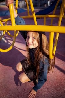 Jolie fille s'amusant sur l'aire de jeux à l'extérieur