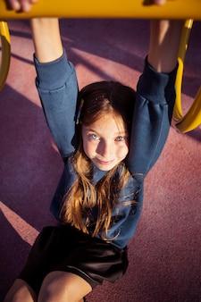 Jolie fille s'amusant sur l'aire de jeux en plein air