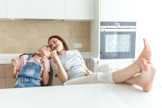 Jolie fille et sa mère sourient en mangeant des glaces dans la cuisine avec les jambes sur une table