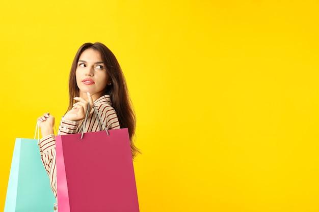 Jolie fille avec des sacs en papier multicolores sur fond jaune.