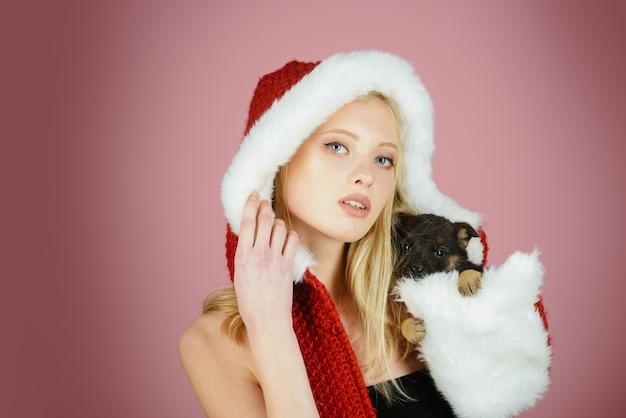 Jolie fille de santa avec un maquillage naturel tient un mignon petit chiot à la main. noël, concept de célébration du nouvel an - jolie femme blonde vêtue d'un chapeau de père noël et d'un petit chien la veille de noël.