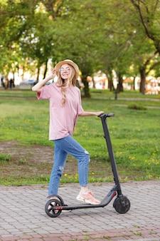 Jolie fille avec un scooter électronique dans un parc de la ville en été