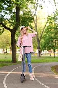 Jolie fille avec scooter sur la piste dans le parc lors d'une promenade