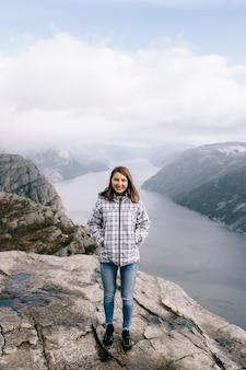 Une jolie fille se dresse au sommet du mont preikestolen (pulpit rock) en norvège