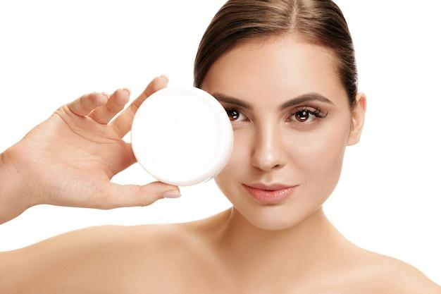 Jolie fille se prépare à commencer sa journée. elle applique une crème hydratante sur le visage au studio. le concept de beauté, soins, peau, traitement, santé, spa, cosmétique et publicité