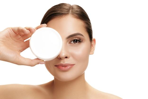 Jolie fille se prépare à commencer sa journée. elle applique une crème hydratante sur le visage au studio. le concept beauté, soins, peau, traitement, santé, spa, cosmétique et publicité