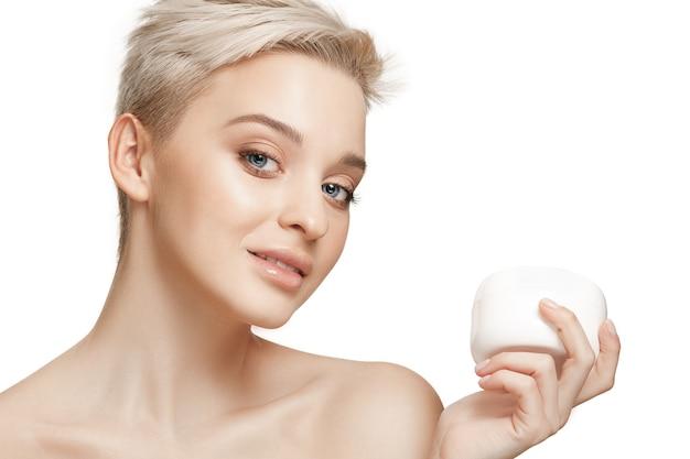 Jolie fille se prépare à commencer sa journée. elle applique une crème hydratante sur le visage à . les soins, la peau, le traitement, la santé, le spa, le concept cosmétique