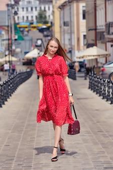 Jolie fille se promène au milieu de la rue en journée ensoleillée