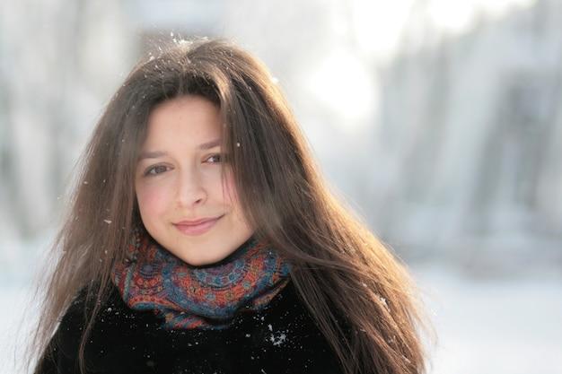 Une jolie fille se promène en hiver à travers la forêt.