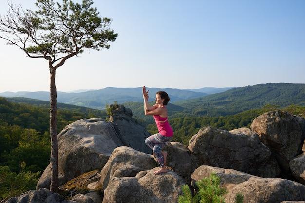 Jolie fille se tient dans une pose de yoga compliquée au sommet d'un gros rocher par une chaude journée d'été
