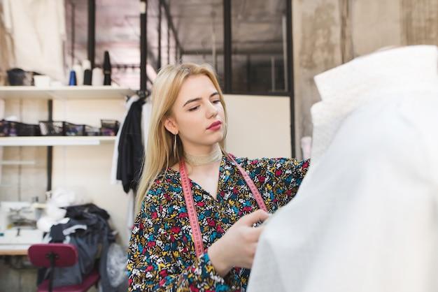 Jolie fille se tient près du mannequin avec des vêtements et travaille.