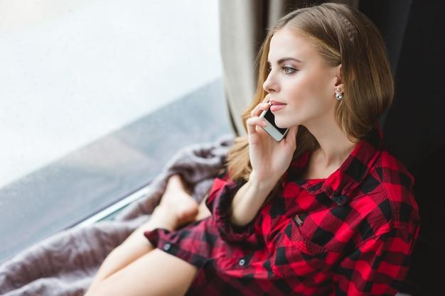 Jolie fille sensuelle en chemise à carreaux parlant au téléphone portable et regardant par la fenêtre