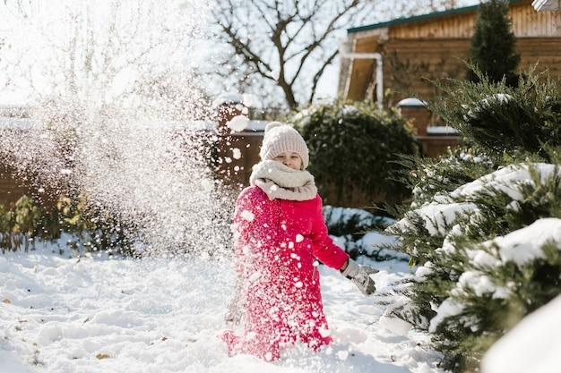 Jolie fille de sept ans en vêtements d'hiver jouant avec de la neige dans la cour d'une maison par une journée ensoleillée d'hiver.