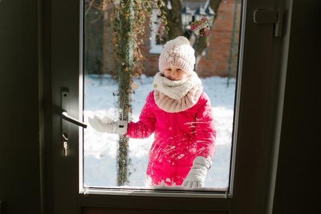 Une jolie fille de sept ans en vêtements d'hiver se tient devant la porte, dans la rue avec de la neige dans les mains et regarde dans la maison en souriant.
