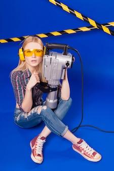 Jolie fille sexy constructeur en chemise à carreaux, jeans et lunettes tiennent le perforateur, asseoir les jambes croisées