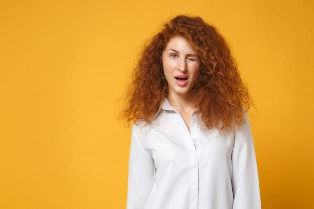 Jolie fille sexy jeune femme rousse en chemise blanche décontractée posant isolée sur un mur orange jaune