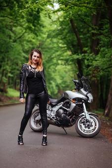 Une jolie fille sexy vêtue de cuir posant près d'une moto de sport à l'extérieur