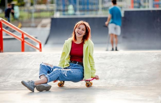Jolie fille avec skateboard assis et souriant. adolescente patineuse près de la rampe d'équitation du parc