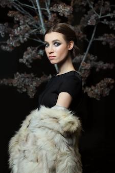 Jolie fille en soirée maquillage et abaissé manteau de fourrure sur dark