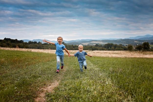 Jolie fille avec son frère courant ensemble dans une belle prairie dans les montagnes