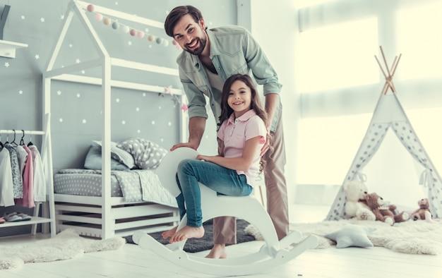 Jolie fille et son jeune papa regardent la caméra.
