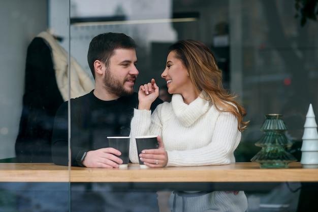 Jolie fille avec son petit ami assis dans un café et buvant du café chaud parfumé alors qu'il fait froid. amour et romance