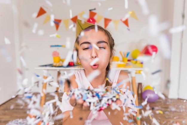 Jolie fille soufflant des confettis de papier sur sa main