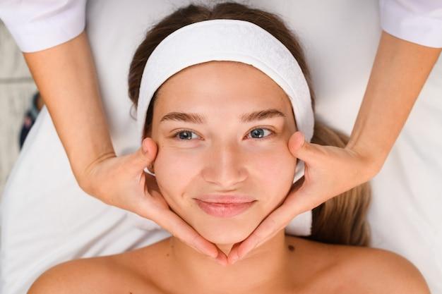 Jolie fille souriante allongée sur un canapé cosmétologique avec un bandage de serviette de cheveux et des mains d'esthéticienne massent son visage vue de dessus
