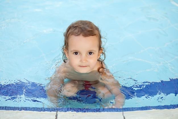 Jolie fille souriante et assise dans la piscine
