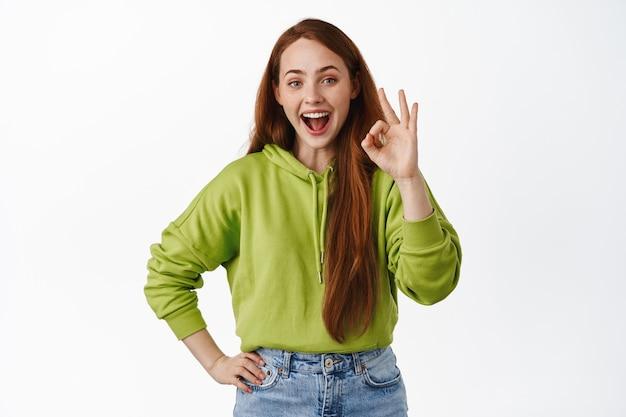 Une jolie fille souriante au gingembre montre le signe ok ok, bon travail, loue quelque chose de gentil, approuve une bonne chose, recommande sur blanc