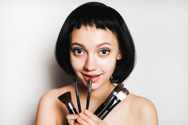 Jolie fille souriante aux cheveux noirs tient dans ses mains des pinceaux de maquillage