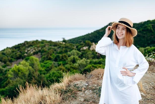 Jolie fille souriante aux cheveux rouges dans un chapeau sur un beau fond de nature, été