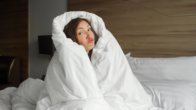 Jolie fille souriante en couverture blanche s'amuse au lit dans la chambre en gros plan du matin