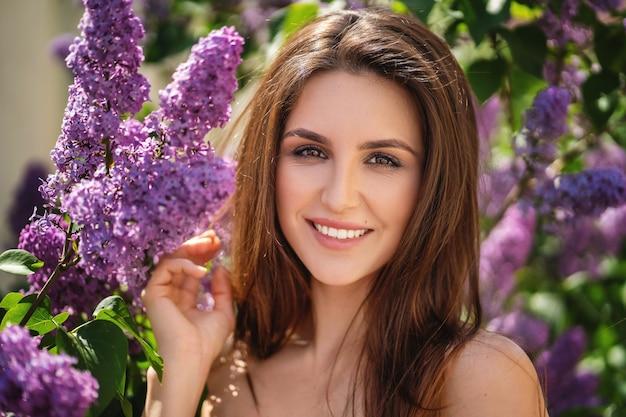 Jolie fille souriante dans les buissons de lilas