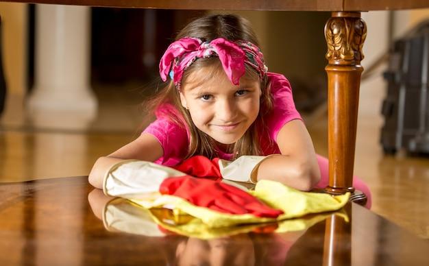 Jolie fille souriante dans des gants en caoutchouc table de nettoyage par chiffon
