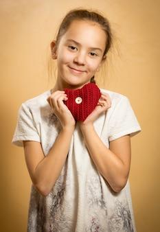 Jolie fille souriante étreignant le coeur tricoté rouge