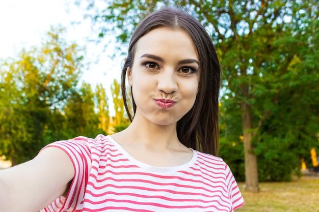 Jolie fille souriante faisant selfie, brune aux cheveux longs en vêtements blancs