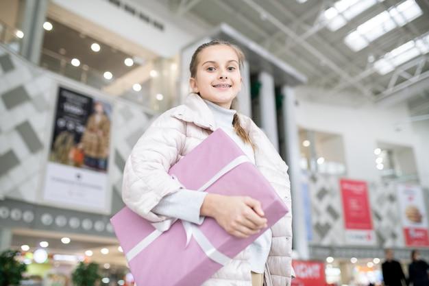 Jolie fille souriante avec une grande boîte cadeau debout devant la caméra dans le centre commercial pendant la vente saisonnière avant noël