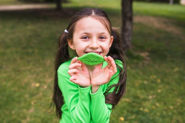 Jolie fille souriante jouant avec une fausse feuille d'argile dans le parc