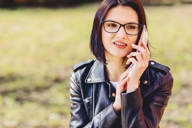 Jolie fille souriante à lunettes parle par téléphone