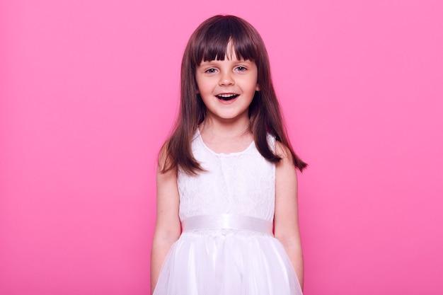 Jolie fille souriante portant une robe blanche regardant directement à l'avant avec une expression faciale heureuse, ayant les cheveux noirs, une humeur positive, isolée sur un mur rose