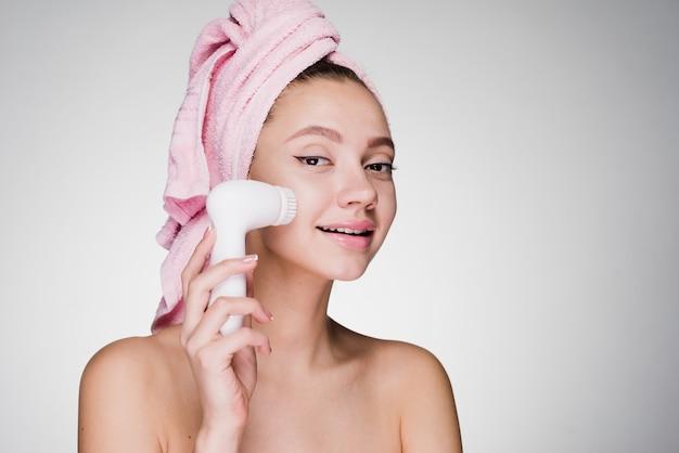 Jolie fille souriante avec une serviette rose sur la tête nettoie la peau de son visage avec une brosse électrique